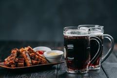 黑啤酒和开胃啤酒快餐 与两个杯子的表sto 库存图片