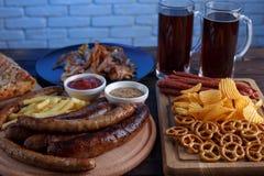 黑啤酒和开胃被设置的啤酒快餐 关闭两个杯子o 免版税库存图片
