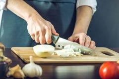 黑围裙的厨师切与刀子的一棵葱 环境友好的产品的概念烹调的 免版税图库摄影