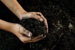 黑土壤在儿童手上 免版税库存照片