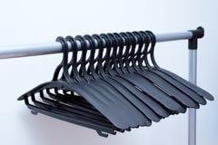 黑塑料挂衣架在轻的背景垂悬 许多不同的挂衣架 库存图片