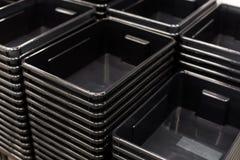 黑塑胶容器堆在商店 免版税库存照片