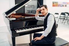 黑大平台钢琴的专业钢琴演奏家 库存图片