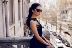 黑太阳镜的坚强,端庄的妇女,性感的黑礼服,头发马尾辫,看与态度阳台 免版税库存图片