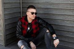 黑太阳镜的好年轻行家人有在一件时髦红色格子花呢披肩夹克的一种时髦的发型的在灰色被剥去的牛仔裤 免版税图库摄影