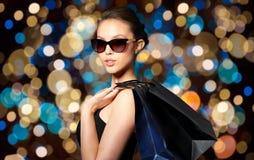 黑太阳镜的愉快的妇女有购物袋的 库存图片