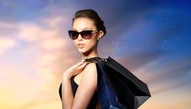 黑太阳镜的愉快的妇女有购物袋的 免版税库存图片