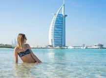 黑太阳镜的美丽的女孩坐在蓝色海和天空背景的白色沙子海滩  暑假和假期-女孩 库存照片