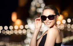 黑太阳镜的美丽的妇女在圣诞节 免版税库存图片