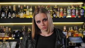 黑夹克的年轻美丽的妇女有重的做看直接在照相机,船尾,被确定,酒吧背景 股票录像