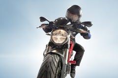 黑夹克的骑自行车的人和盔甲坐他的在蓝色背景的嬉戏自行车 库存照片