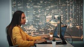 黑女性videographer侧视图与英尺长度和声音一起使用在计算机上有两显示的