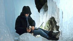 黑客乱砍服务器 编程的人在膝上型计算机在冰洞 在神奇冰洞穴附近 人在a掩藏自己 影视素材