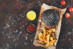 黑小圆面包汉堡用土豆楔住顶视图 库存图片