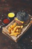 黑小圆面包汉堡用土豆楔住顶视图 免版税图库摄影