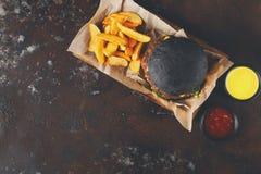 黑小圆面包汉堡用土豆楔住顶视图 库存照片