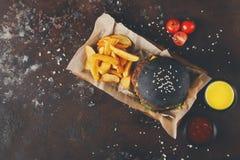 黑小圆面包汉堡用土豆楔住顶视图 免版税库存照片