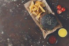 黑小圆面包汉堡用土豆楔住顶视图 图库摄影