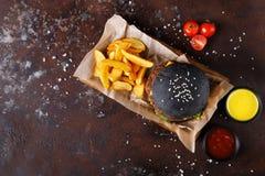 黑小圆面包汉堡用土豆楔住顶视图 免版税库存图片