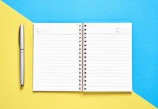 黑屏幕在淡色黄色和蓝色背景安置的笔记本空白和笔 库存照片