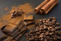 黑巧克力片、桂香和咖啡豆,从溢出的巧克力平板磨碎了在板岩盘的巧克力粉末 关闭 库存图片