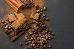 黑巧克力片、桂香和咖啡豆,从溢出的巧克力平板磨碎了在板岩盘的巧克力粉末 顶视图 免版税库存照片