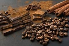 黑巧克力片、桂香和咖啡豆,从溢出的巧克力平板磨碎了在黑盘的巧克力粉末 关闭 免版税库存照片