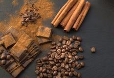 黑巧克力片、桂香和咖啡豆,从溢出的巧克力平板磨碎了在黑盘的巧克力粉末 顶视图 免版税库存图片