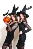 黑巫婆万圣夜服装的两名愉快的妇女用在党的南瓜在白色背景 免版税库存照片