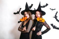 黑巫婆万圣夜服装的两名愉快的妇女用在党的南瓜在白色背景 免版税库存图片