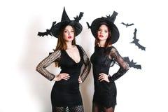 黑巫婆万圣夜服装的两名愉快的性感的妇女在白色背景的党 免版税库存图片