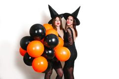 黑巫婆万圣夜服装的两名愉快的性感的妇女有在党的橙色和黑气球的在白色背景 图库摄影