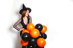 黑巫婆万圣夜服装的愉快的性感的妇女有在党的橙色和黑气球的在白色背景 库存图片