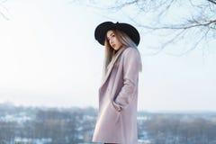 黑帽会议和外套的年轻美丽的女孩在a背景  库存图片