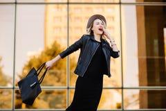 黑帽会议和皮夹克和袋子的愉快的白肤金发的妇女 图库摄影