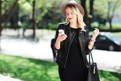 黑帽会议和皮夹克的白肤金发的使用手机的妇女和袋子 免版税库存照片