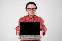 黑帽会议的一位年轻程序员拿着在他的韩的一台膝上型计算机 库存图片