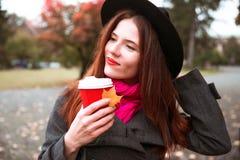 黑帽会议的愉快的妇女有走在秋天城市公园的咖啡的 多雨天气和黄色树 库存照片