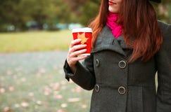 黑帽会议的愉快的妇女有走在秋天城市公园的咖啡的 多雨天气和黄色树 免版税图库摄影