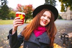 黑帽会议的愉快的妇女有走在秋天城市公园的咖啡的 多雨天气和黄色树 免版税库存照片