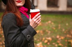 黑帽会议的愉快的妇女有走在秋天城市公园的咖啡的 多雨天气和黄色树 免版税库存图片