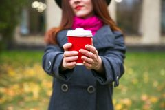 黑帽会议的愉快的妇女有走在秋天城市公园的咖啡的 多雨天气和黄色树 库存图片