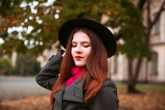 黑帽会议的愉快的妇女走在秋天城市公园的 多雨天气和黄色树 库存照片
