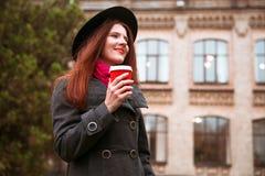 黑帽会议的愉快的妇女走在秋天城市公园的 多雨天气和黄色树 免版税库存照片