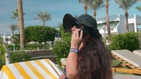 黑帽会议的晒日光浴白种人资深女性的老人谈话在智能手机和在阳光下坐轻便折叠躺椅 影视素材