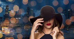 黑帽会议的美丽的妇女在夜城市 免版税图库摄影