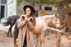 黑帽会议的美丽的少妇有户外一匹棕色马的 免版税库存图片