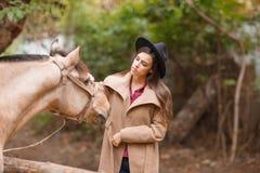 黑帽会议的美丽的少妇有户外一匹棕色马的 库存图片
