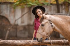 黑帽会议的美丽的少妇有户外一匹棕色马的 图库摄影
