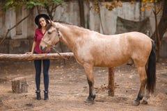 黑帽会议的美丽的少妇有户外一匹棕色马的 库存照片